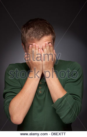 Teenager boy man portrait shy hands covering face - Stock Photo