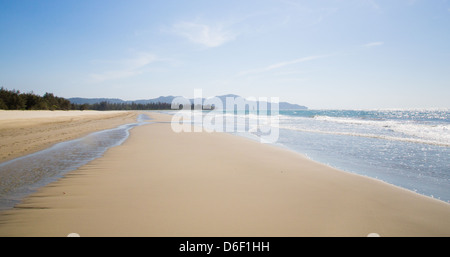 Wide deserted white sand beach at Rasa Ria near Kota Kinabalu in Malaysian Borneo bordering the South China Sea - Stock Photo