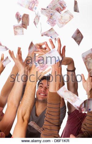 Teenagers money raining falling sky Euros happy - Stock Photo