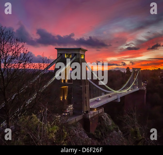 Clifton Suspension Bridge over the Avon Gorge Bristol illuminated at dusk with a colourful western sunset - Stock Photo