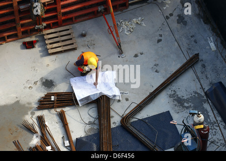 Berlin, Germany, a worker studying the blueprint at a construction site at the Zoo - Stock Photo