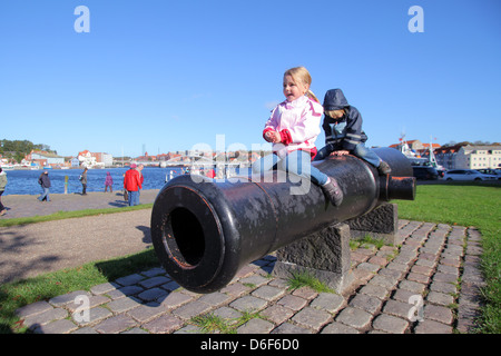 Sønderborg, Denmark, two children sitting on a historic cannon - Stock Photo