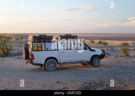Safari equipped Toyota Hilux 4x4 on Kubu Island, view on Sua salt pan - Stock Photo