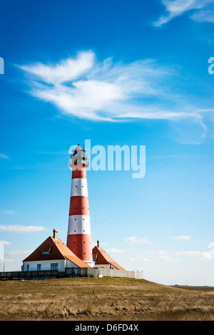 Vertical image of the lighthouse westerhever on a sunny day with blue sky and white clouds.