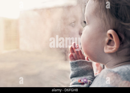 Cute infant girl looking out window - Stock Photo