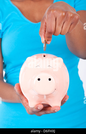 Black african american woman inseerting coin inside a smiling Piggy bank isolated on white background - African - Stock Photo