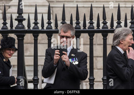 Dignitaries leave the funeral service of Baroness Margaret Thatcher at St Paul's Cathedral. A guest pauses to take - Stock Photo
