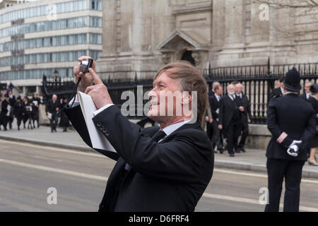 A guest pauses to take a photograph as dignitaries leave the funeral service of Baroness Margaret Thatcher at St - Stock Photo