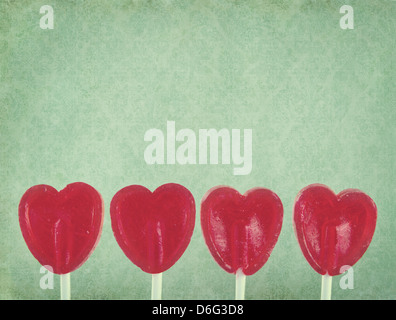 Row of red lollipop hearts on green vintage background with copy space