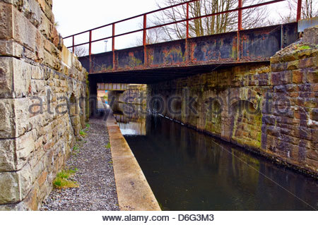 the disused tennant canal and towpath under the vale of neath railway bridges near skewen neath - Stock Photo