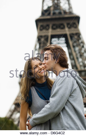 Young couple kissing with Eiffel tower in background Paris France - Stock Photo