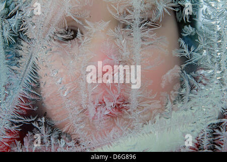 An illustration shows a child behind frostwork on a window in Wernigerode, Germany, 11 February 2012. Photo: Matthias - Stock Photo