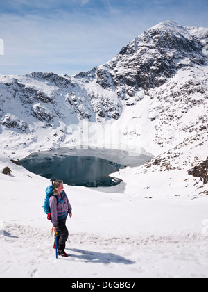 Snowdon in winter conditions - a female hill walker on the Pyg track with a view to the summit, Yr Wyddfa, over - Stock Photo