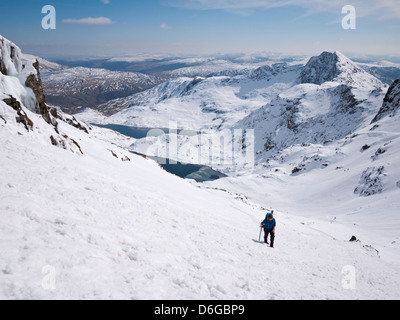 Snowdon in winter conditions - a female hill walker heads up the Pyg track to the summit - Stock Photo
