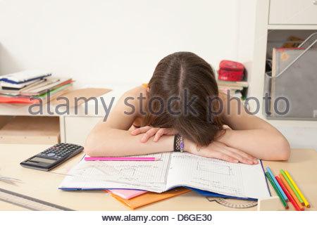 Girl sleeping desk with homework - Stock Photo