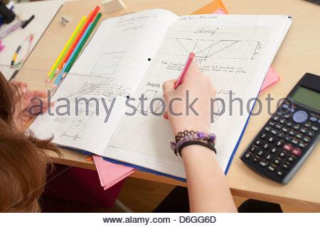 Close up girl doing math's homework - Stock Photo