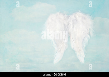 White angel wings on textured blue sky background, with copy space - Stock Photo