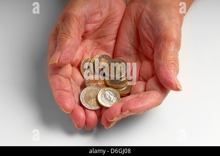 Older woman holding Euro coins - Stock Photo