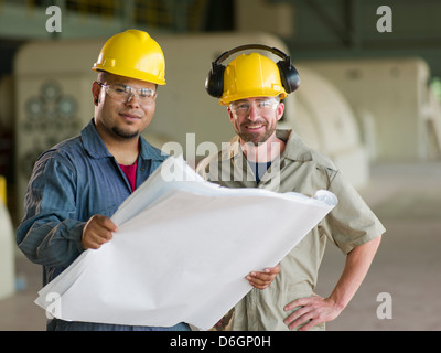 Engineers reading blueprints on site - Stock Photo