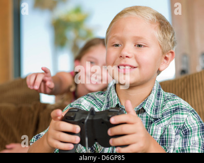 Children playing video games on sofa - Stock Photo