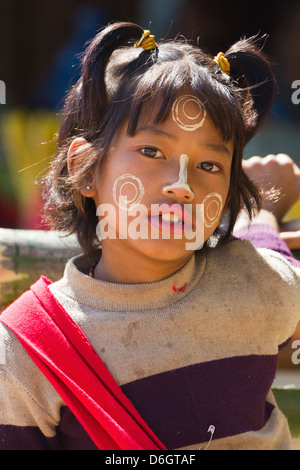 Cheeky little girl with Thanaka face decorations in Inn Thein Village, Myanmar 1 - Stock Photo