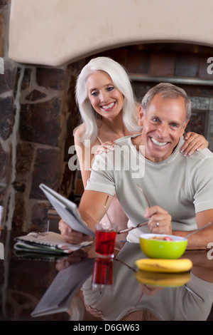 Older couple smiling at breakfast - Stock Photo