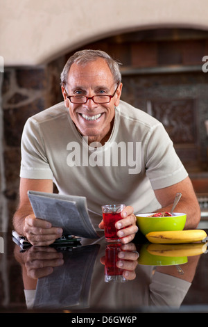 Older man reading newspaper at breakfast - Stock Photo