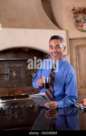 Businessman with newspaper at breakfast - Stock Photo