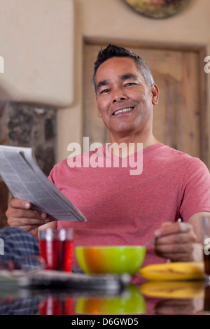 Man reading newspaper at breakfast - Stock Photo