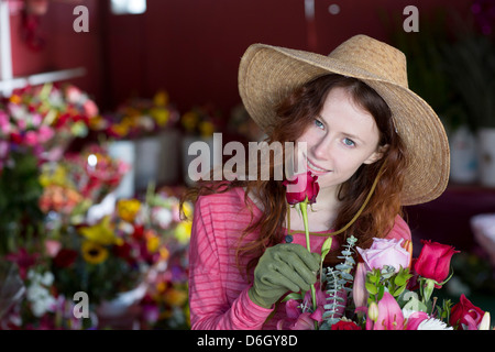 Florist smelling flowers in shop - Stock Photo