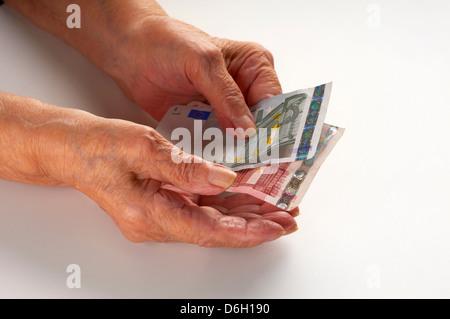 Older woman holding Euro notes - Stock Photo