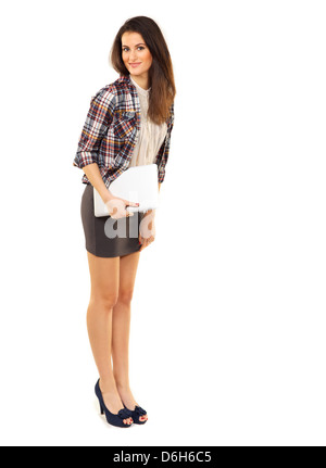 College student in the studio standing while holding her laptop - Stock Photo