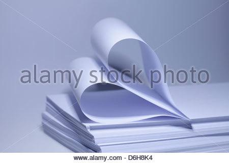 Sheets Paper folded in heart shape - Stock Photo