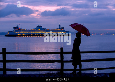 Woman with umbrella admiring cruise ship - Stock Photo