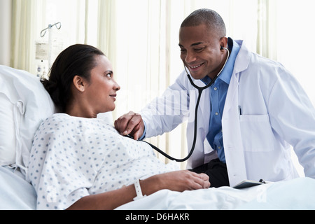 Male doctor checking female patient with stethoscope - Stock Photo