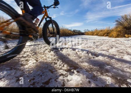 Mountain biker on snow in rural field - Stock Photo