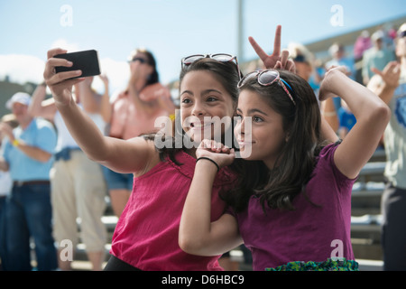 Girls taking a picture of themselves at pop concert - Stock Photo