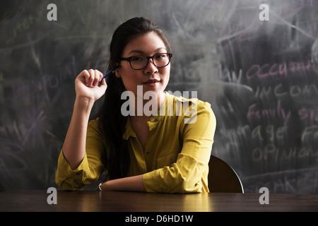 Portrait of woman in front of blackboard - Stock Photo