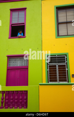 Boy looking out window of colourful house, Bo-Kaap, Cape Town, South Africa - Stock Photo