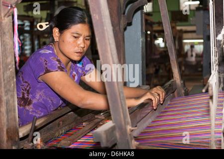 Woman weaving on a loom, Thein Nyo silk weaving workshop, Amarapura, Mandalay, Myanmar, (Burma) - Stock Photo