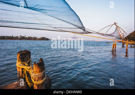 Chinese fishing net flutters in the breeze in Fort Kochi harbour, Kerala, India. - Stock Photo