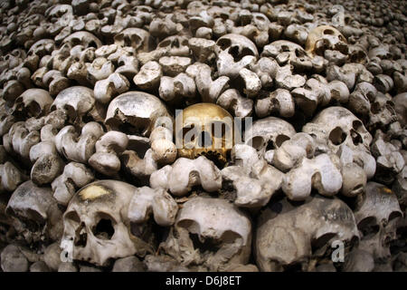 Bones and skulls are stacked on each other in the ossuary ...