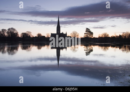 Salisbury cathedral at dawn reflecting in the flooded West Harnham Water Meadows, Salisbury, Wiltshire, England, - Stock Photo