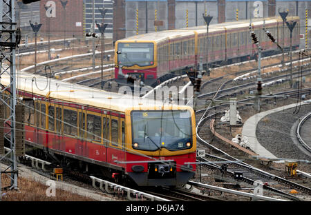An S-Bahn line 75 train waits behind an S5 train at Lichtenberg Station in Berlin,Germany, 10 March 2012. Passengers - Stock Photo