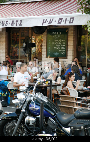 Young people sitting at Sus Etz Cafe in the trendy Sheinkin street, Tel Aviv, Israel, Middle East - Stock Photo