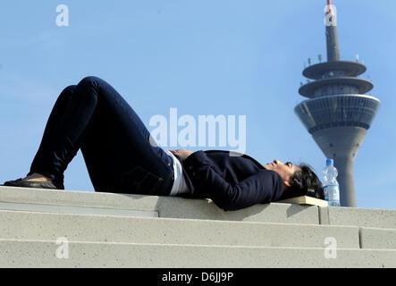 Frühlingsanfang: Eine junge Frau liegt am Dienstag (20.03.2012) in Düsseldorf im Medienhafen bei strahlendem Sonnenschein, - Stock Photo