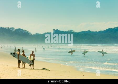 Surfers on Playa Guiones beach, Nosara, Nicoya Peninsula, Guanacaste Province, Costa Rica, Central America - Stock Photo