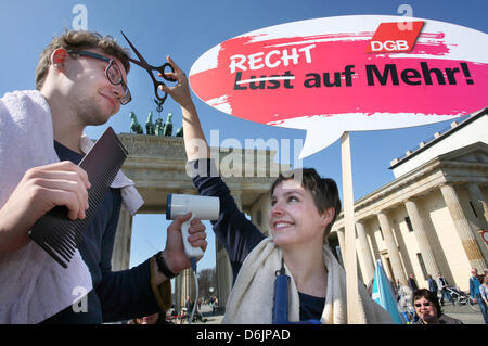 Two protesters dressed as hairdressers hold up a sign which reads 'Recht auf Mehr!' (Rights to more!) during the - Stock Photo