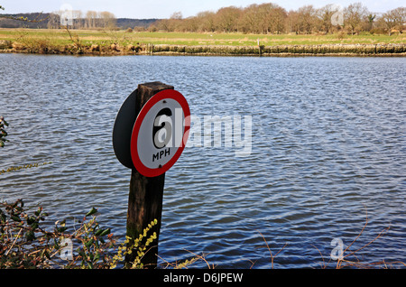 A speed limit sign on the bank of the River Yare at Surlingham, Norfolk, England, United Kingdom. - Stock Photo