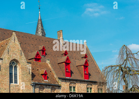 Top of the old brick house and the church in Bruges, Belgium - Stock Photo